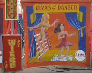 Divas of Danger painted sign with two women walking on swords and broken glass