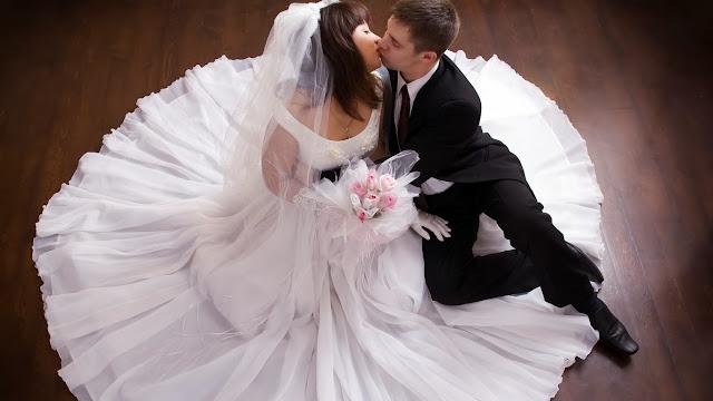 жених целует невесту в красивом платье