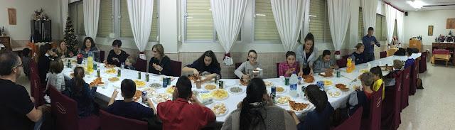la imagen muestra una mesa larga con todos los alumnos y familias comiendo pizzas