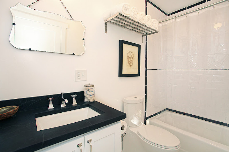Master bathroom with white cabinets, black counter top and white subway tiles in the shower with a black tile trim