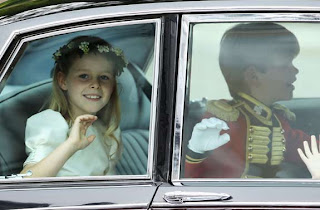 Bridesmaid Margarita Armstrong-Jones and page boy Tom Pettifer wave as they arrive to attend the Royal Wedding