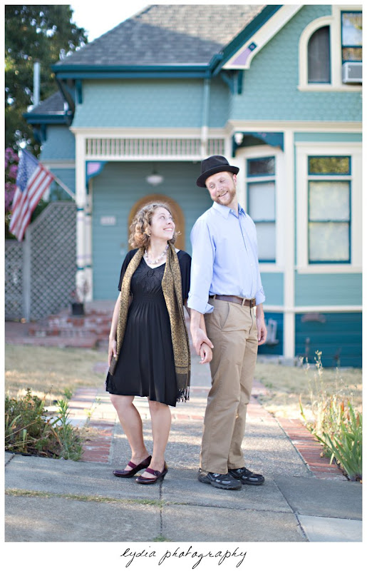 Bride and groom holding hands in front of a cottage at lifestyle engagement portraits in the Bay Area of California