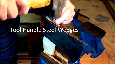 Axe head held in vise while pounding in steel wedges