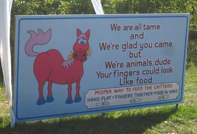 Hand-painted sign with horse cartoon and the following text: We are all tame/and/We're glad you came/but/We're animals, dude/Your fingers could look/Like food