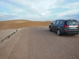 Na zo'n 70 kilometer op de eenzame weg naar de oase blijkt er een 'dijk' van een duin de weg op te zijn 'gewandeld'