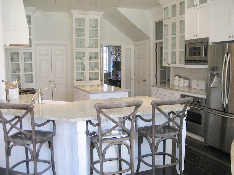 classic white kitchen with classic glass door upper cabinets, Walker Zanger white glazed terra cotta tile backsplash, Kashmir granite countertops, black glazed ceramic tile floors and wood bar stools
