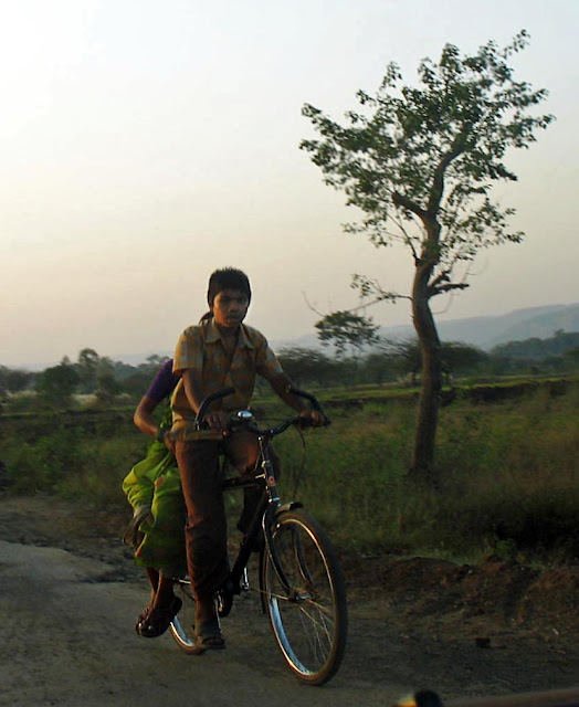 boy ferrying mom on bicycle