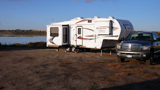 Truck and fifth wheel set up by the lake.
