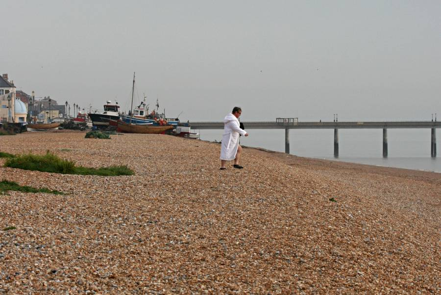 man in white twoelling dressing gown crossing beach