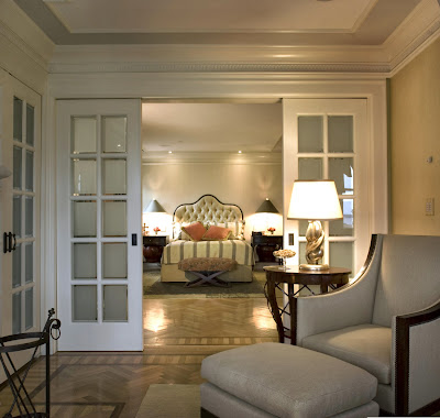 looking the master bedroom with rolling doors, into the traditional style bedroom inside that looks elegant and luxurious