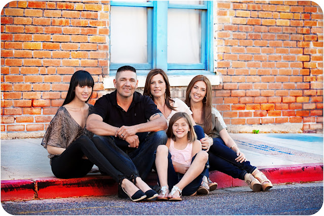 Family of five posing for family photo sitting on a sidewalk curb