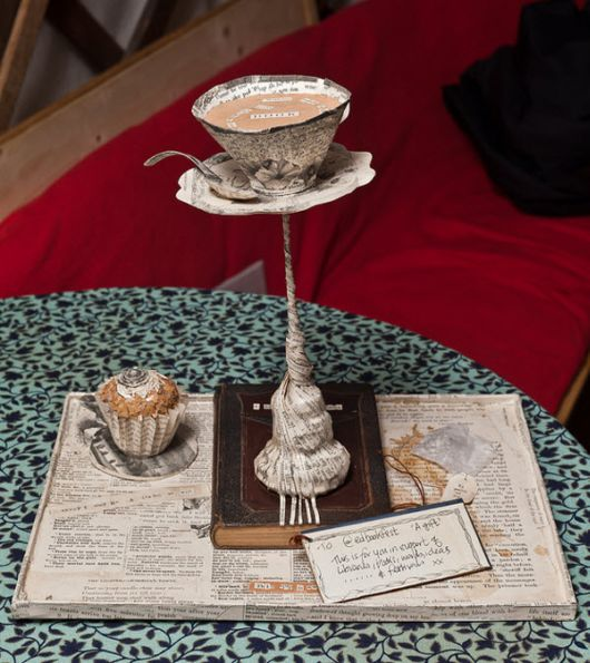 paper sculpture of tea cup and cupcake on a book