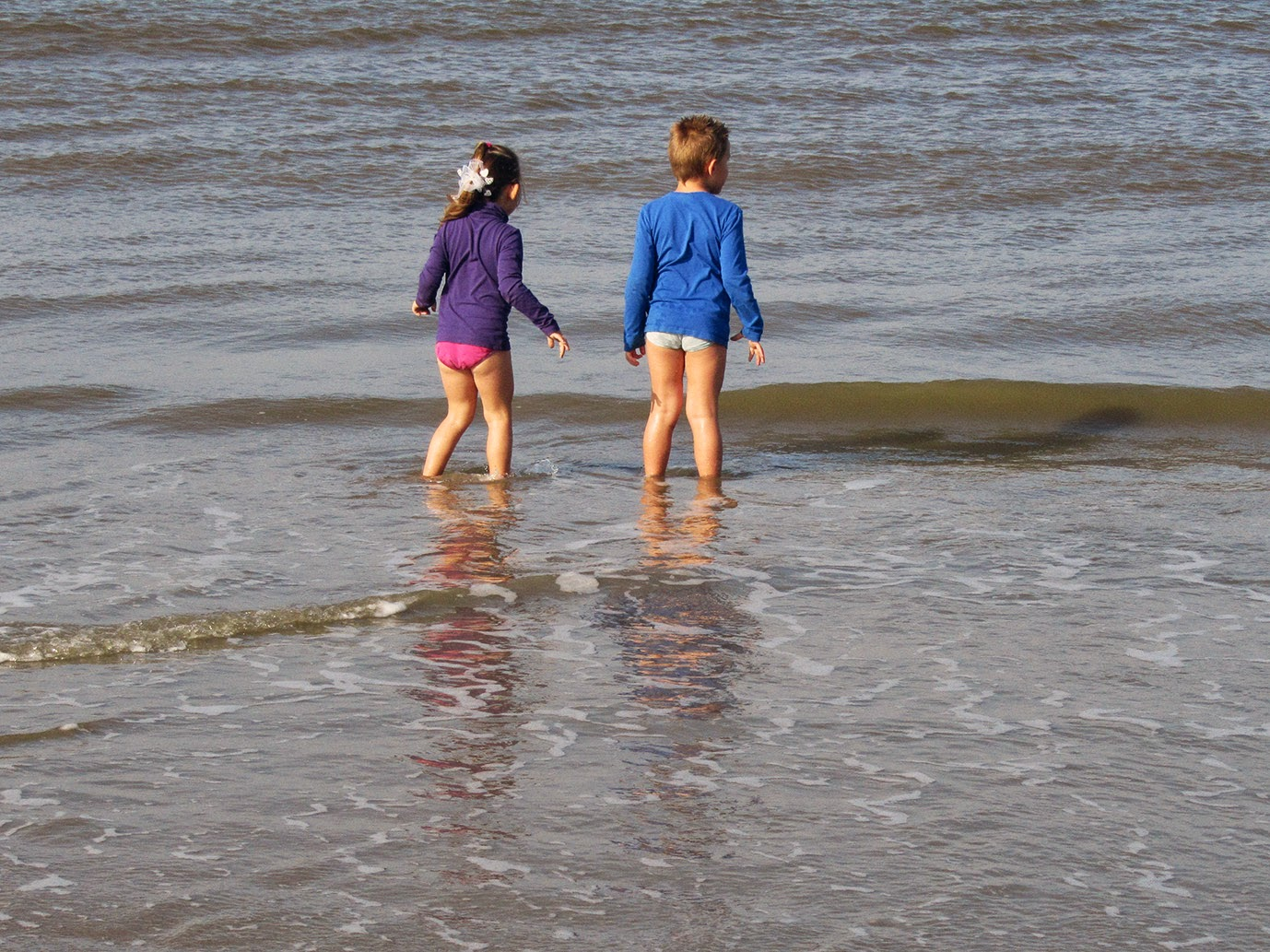 little girl and boy anticipating waves