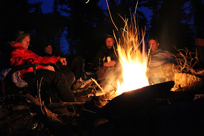 The boys sitting around the campfire