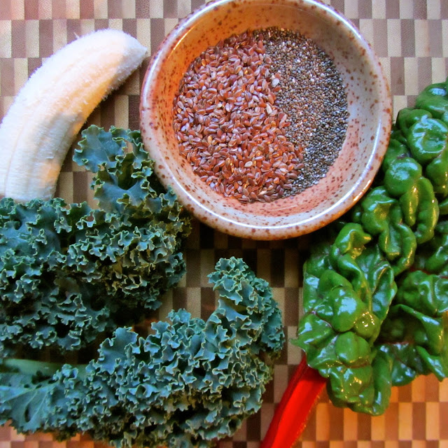 kale, chard, banana, chia and flax seeds arranged on a cutting board