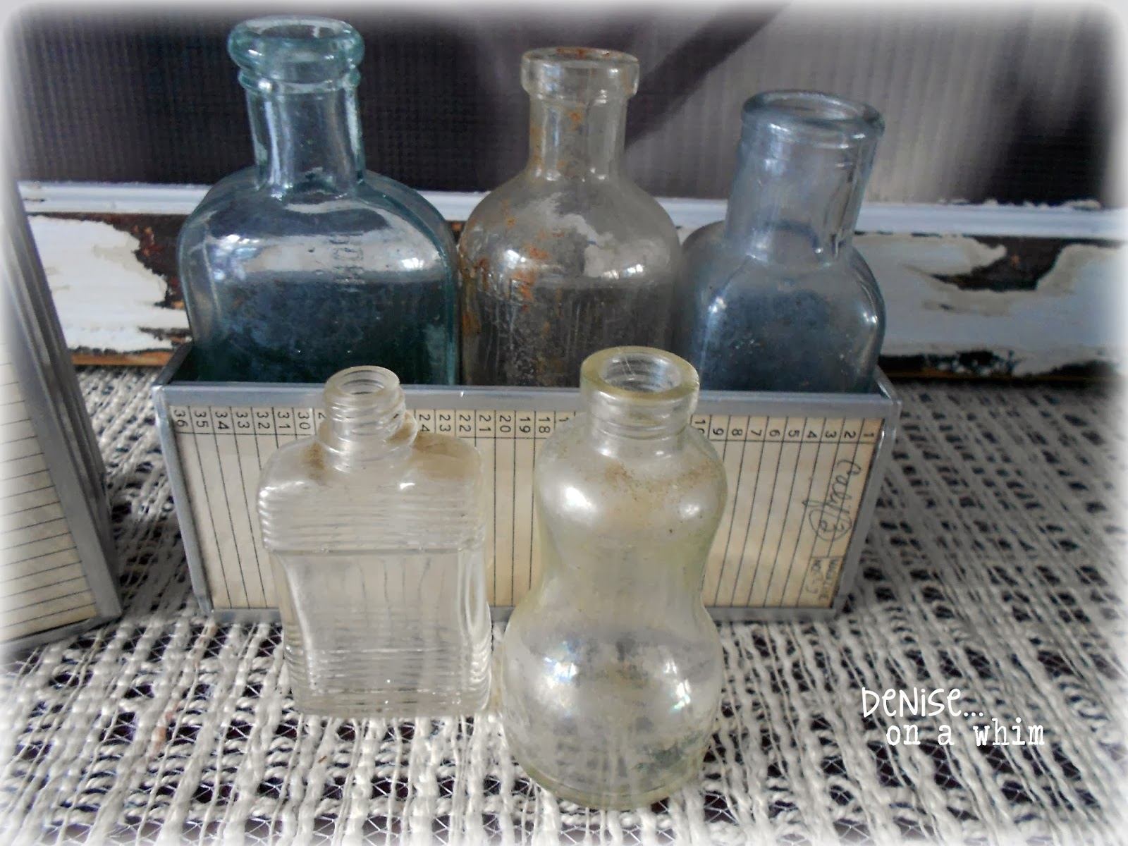 glass bottles and an old slider holder as decor via http:/deniseonawhim.blogspot.com