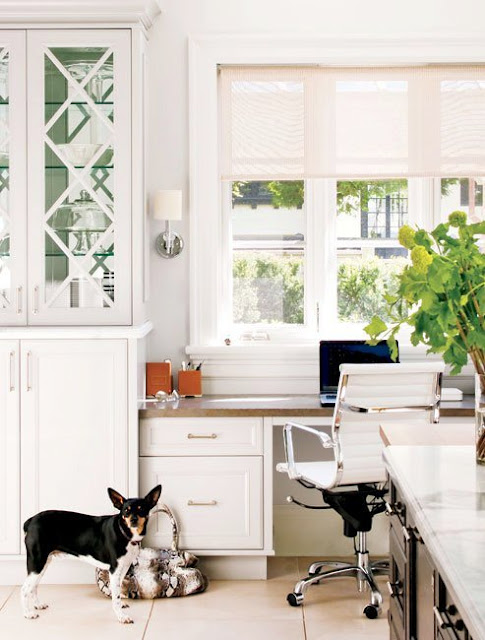 Home office in the kitchen with cabinets, a rolling chair and a white desk facing a window