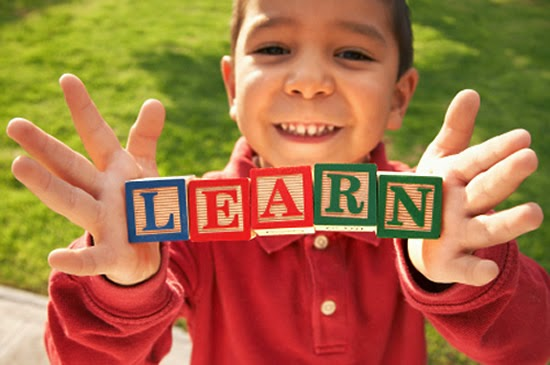 Little boy holding the letters that spell learn