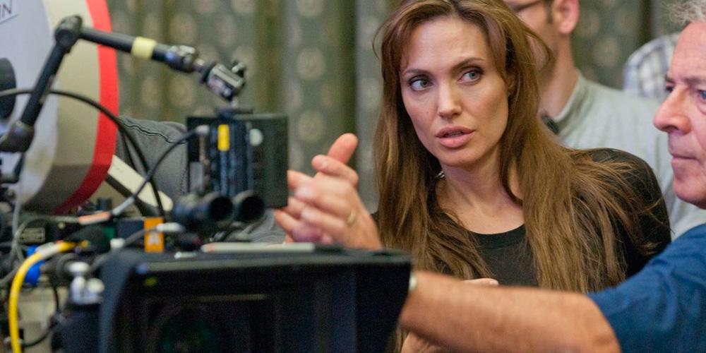 Angelina jolie como diretora no set de filmagens de garota interrompida ao lado de uma câmera cinematográfica com sua equipe a sua volta