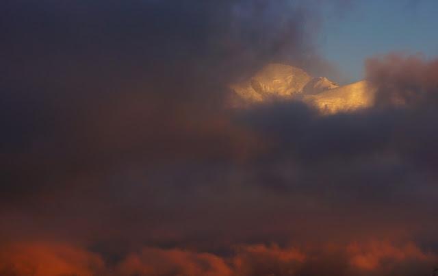 les nuages sont éclairés par le soleil couchant et le sommet du Mont-Blanc se dégage légèrement