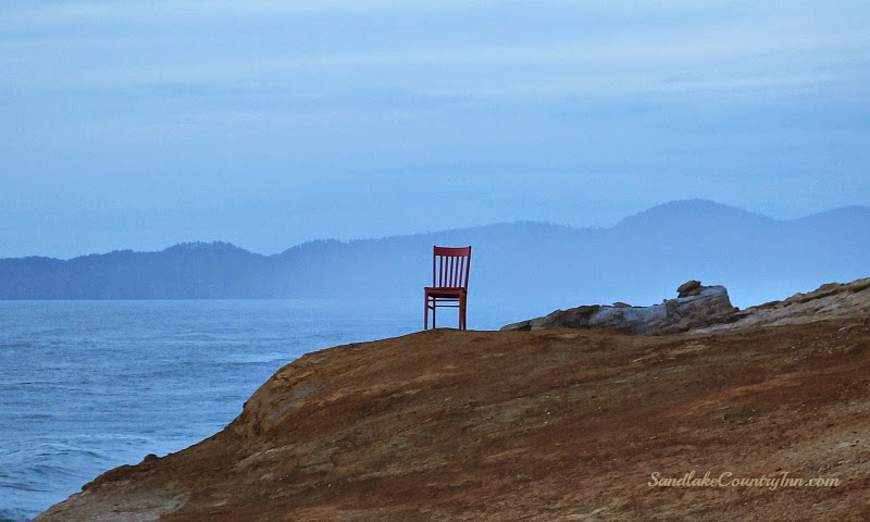 red chair sitting on Cape Kiwanda overlooking Pacific Ocean