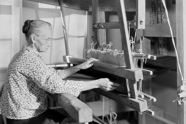 Elderly woman weaving on a loom.