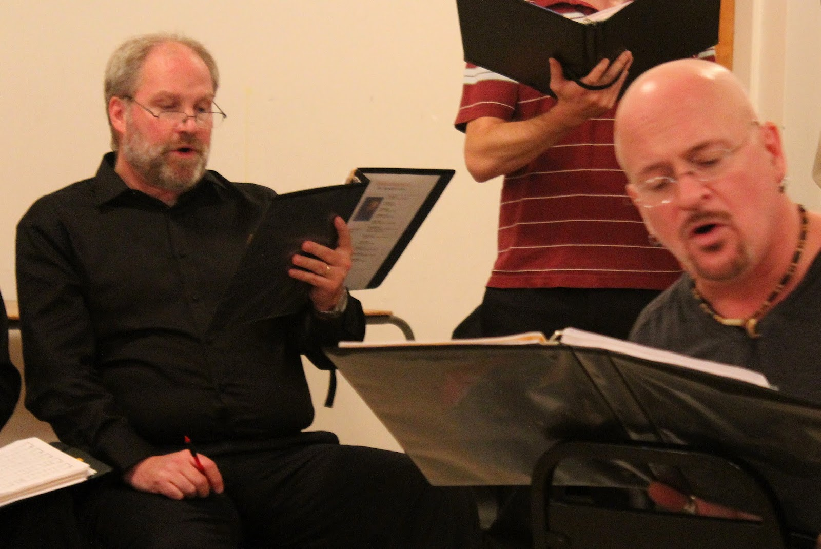 David, at left, pen at the ready, works hard at rehearsal -- while Pierre directs from the center of the circle