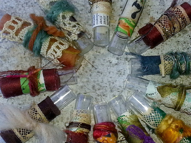 closeup of fiber arts collage on recycled glass vials