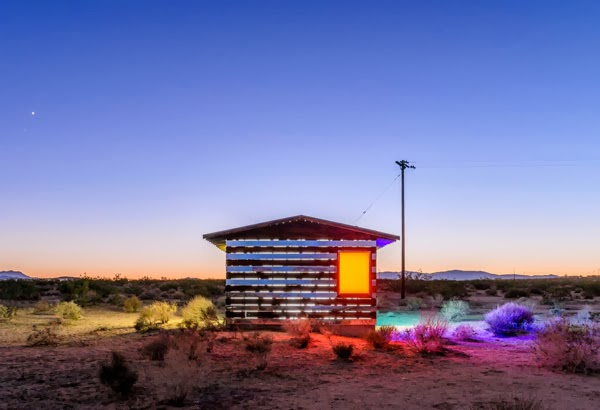 mirror house in desert with orange glowing window