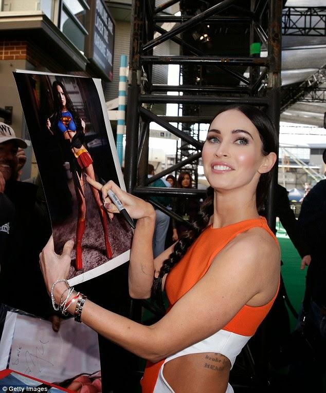 Megan Fox shows off her tattoos in bright orange cut-out dress at Teenage Mutant Ninja Turtles première