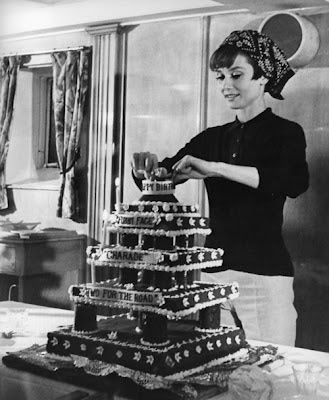 Audrey Hepburn decorating a cake for Stanley Donen