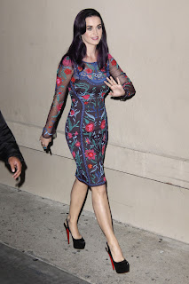 Katy Perry wearing a floral dress and smiling at the fans