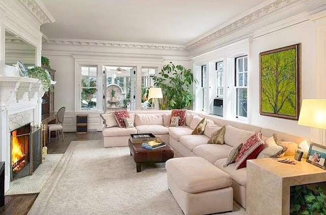 Living room in a mansion sectional sofa white molded fireplace leather ottoman Copper Beech Farm
