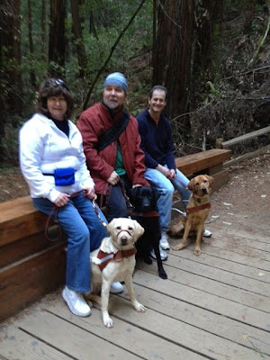 Cecilia with yellow Lab, Yonah with black Lab and Jeff with yellow Lab on a bench