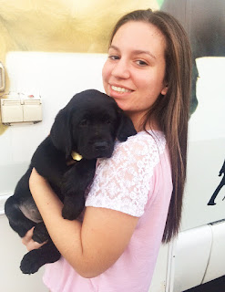 Jaclyn smiles holding a young black Lab puppy in front of the Puppy Truck.