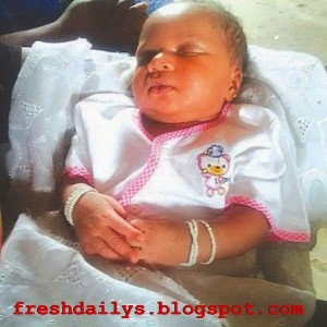 Baby Born With White Traditional Beads in Her Hands