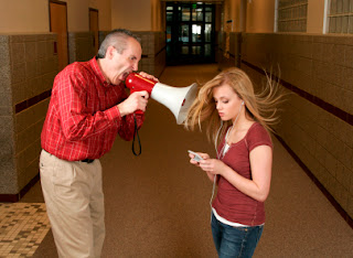 teacher yelling at student on phone with earbuds in with megaphone
