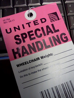 "United Airlines wheelchair tag. Top is pink with black lettering that says ""United Special Handling"" with a white bottom with black text reading ""wheelchair weight, location of key/switch"" and blank lines."