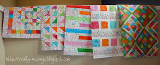 five pretty quilts, all in a row... but they still need binding