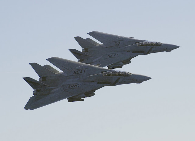 "A pair of F-14D Tomcats flyby with the text ""Go Navy"" ""Beat Army"" on top of  the wings."