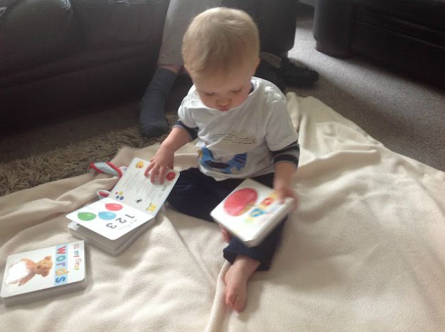 baby on floor with 3 books. abc book in his hand