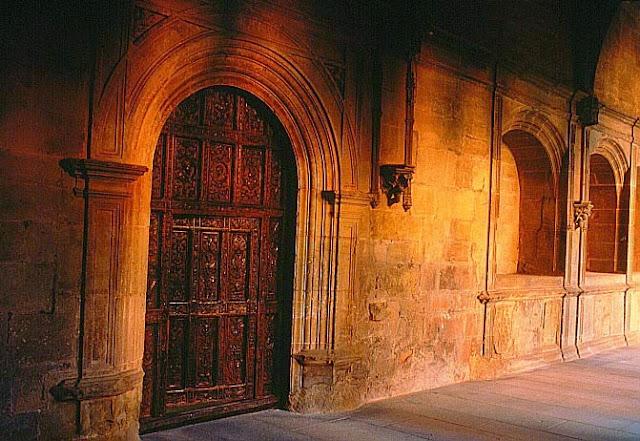 Imagen de una puerta antigua de madera, de corte semicircular y adornos labrados