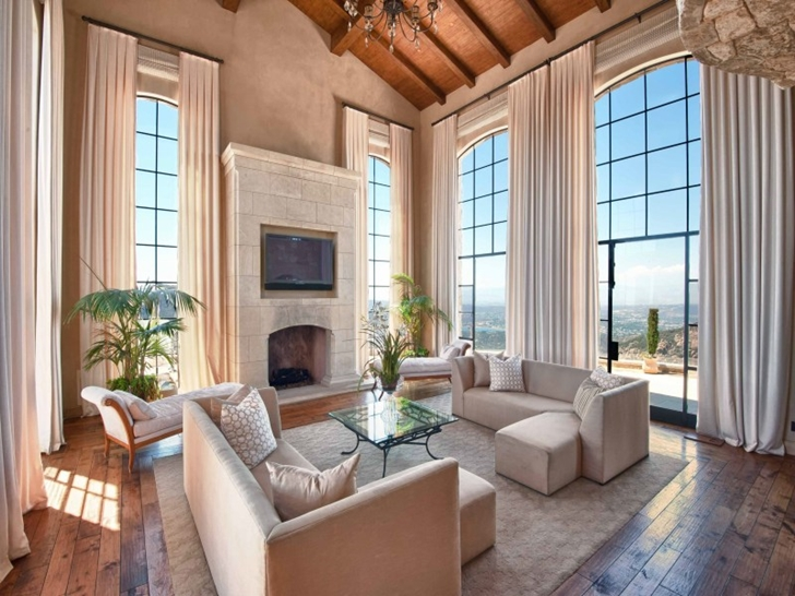 Living room with glass walls in Mediterranean style vineyards home in Malibu