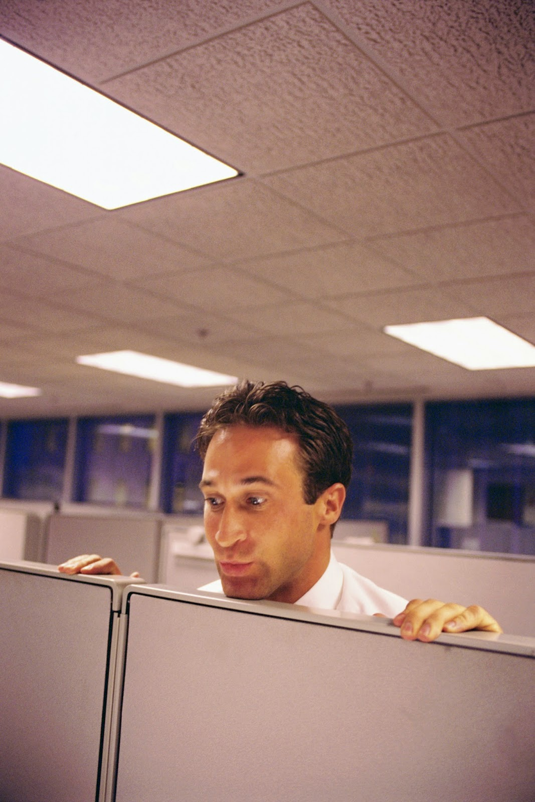 Man peering over cubicle wall