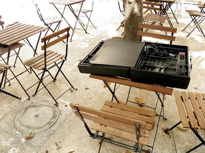Ein aufgeklappter Dolmetschkoffer auf einem Holztisch, drumherum weitere Tische und Stühle. Es ist hell.