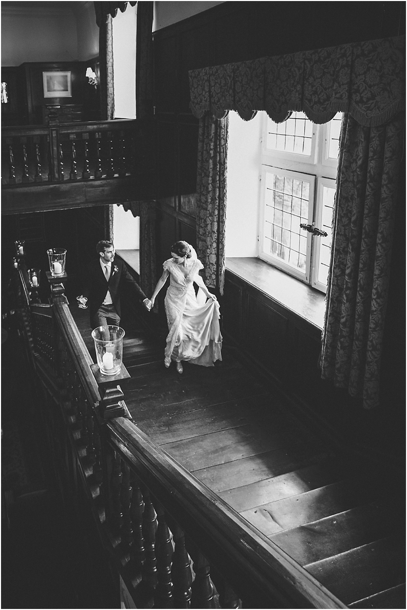 Bride and groom walk up stairs at Brympton House