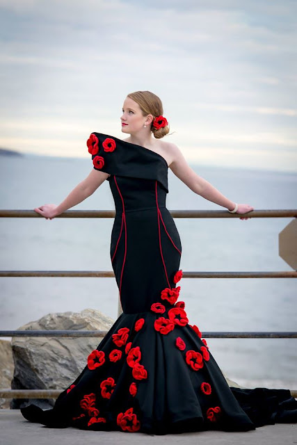Black evening dress with fishtail skirt and embellished with crocheted and knitted poppies. The model is wearing her hair in a low bun decorated with a poppy.