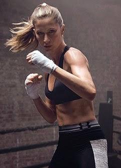 A top model exibe sua ótima forma física e aparece suada vestindo luvas de boxe e golpeando com toda sua força um saco de pancadas