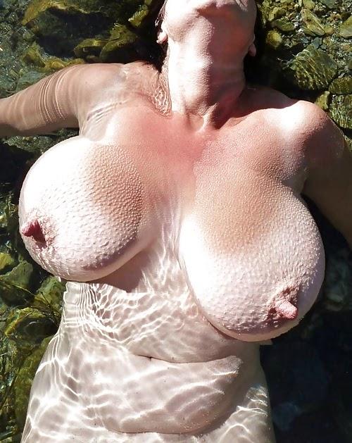 torse de femme nue dans l'eau froide tendant ses magnifiques gros tétons
