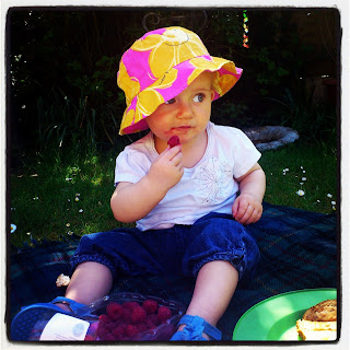 toddler eating raspberries on picnic blanket